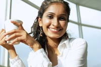 Woman smiling at camera, holding mug - Asia Images Group