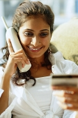Woman using cordless phone and looking at credit card - Asia Images Group