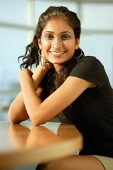 Woman smiling at camera, hand on head, arms crossed - Asia Images Group