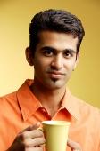 Man looking at camera, mug in hand - Asia Images Group