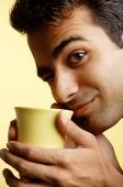 Man holding mug close to face, winking - Asia Images Group