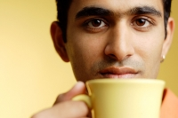Man holding mug to mouth - Asia Images Group