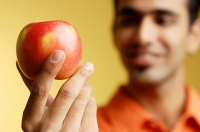 Man holding apple in hand, selective focus - Asia Images Group