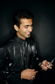 Man looking at mobile phone, smiling - Asia Images Group