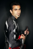 Man holding guitar, portrait - Asia Images Group