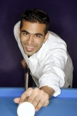 Young man playing pool, smiling at camera - Asia Images Group
