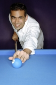 Young man playing pool, smiling at camera, portrait - Asia Images Group
