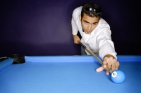 Young man preparing to hit pool ball - Asia Images Group
