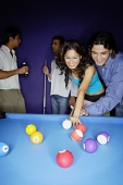 Young adults playing pool, man teaching woman to aim - Asia Images Group