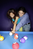 Couple playing pool, man teaching woman how to play - Asia Images Group