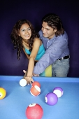 Man teaching woman how to play pool - Asia Images Group
