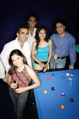 Young adults standing around pool table - Asia Images Group