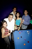 Young adults standing around pool table, smiling at camera - Asia Images Group
