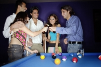 Young adults standing around pool table, toasting with beer bottles - Asia Images Group