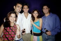 Young adults standing together, holding pool cue and beer bottles, smiling at camera - Asia Images Group