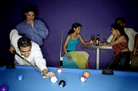 Young adults playing pool, people in the background having beer - Asia Images Group