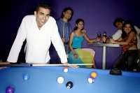 Young man standing at pool table, people in the background, all looking at camera - Asia Images Group