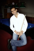 Young man leaning against pool table, holding pool cue - Asia Images Group
