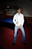 Young man leaning against pool table, smiling - Asia Images Group