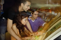 Young adults in amusement arcade, playing games - Asia Images Group