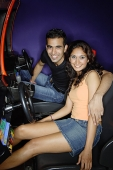 Couple in a video game arcade, smiling at camera - Asia Images Group