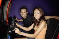 Couple in a video game arcade, playing games, smiling at camera - Asia Images Group