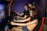 Young adults playing games in video arcade - Asia Images Group