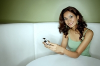 Young woman sitting in booth, looking at mobile phone - Asia Images Group