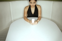 Young woman sitting in booth holding mobile phone - Asia Images Group