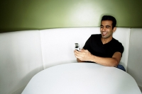 Young man sitting in booth, looking at mobile phone - Asia Images Group