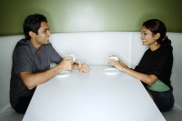 Couple sitting opposite from each other, having tea - Asia Images Group