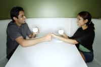 Couple sitting opposite from each other, having tea, holding hands - Asia Images Group