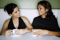 Two women sitting side by side having tea - Asia Images Group