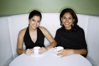 Two women having tea, looking at camera - Asia Images Group
