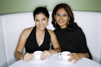 Two women  sitting side by side, having tea, looking at camera - Asia Images Group