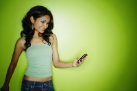 Young woman in green tank top, looking at mobile phone - Asia Images Group