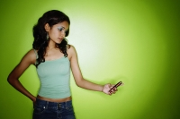 Young woman standing against green wall, looking at mobile phone - Asia Images Group