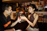 Couple in a club, toasting with cocktails - Asia Images Group
