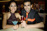 Couple in a club with drinks, smiling at camera - Asia Images Group