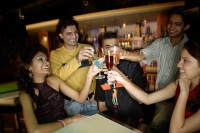 Young adults in club, toasting with drinks - Asia Images Group