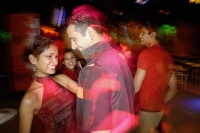 Young people dancing in night club, couple in the foreground - Asia Images Group