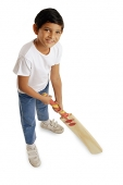 Boy holding cricket bat, smiling at camera - Asia Images Group