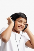 Boy wearing headphones, eyes closed - Asia Images Group
