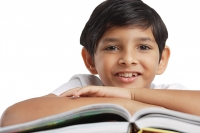 Boy leaning on book, looking at camera - Asia Images Group