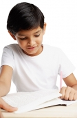 Boy with book and pencil, writing - Asia Images Group