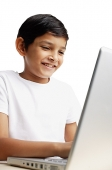 Boy using laptop, smiling - Asia Images Group