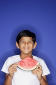 Boy looking at camera, holding watermelon slice - Asia Images Group