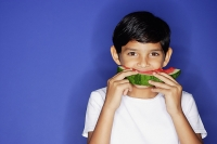 Boy looking at camera, eating watermelon - Asia Images Group