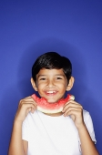 Boy holding slice of watermelon - Asia Images Group