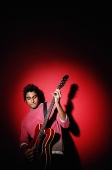 Young man playing guitar, standing against red background - Asia Images Group